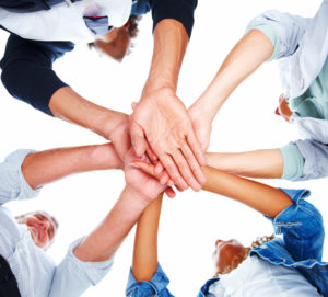 Upward view of a group of people with their hands together on a white background